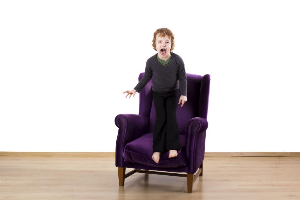 肘掛け椅子に叫んで怒っている子供の癇癪
